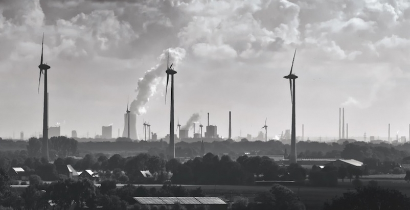 Smokestacks and wind turbines in a rural area