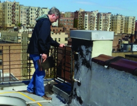 Facilities professional inspects a roof railing system.