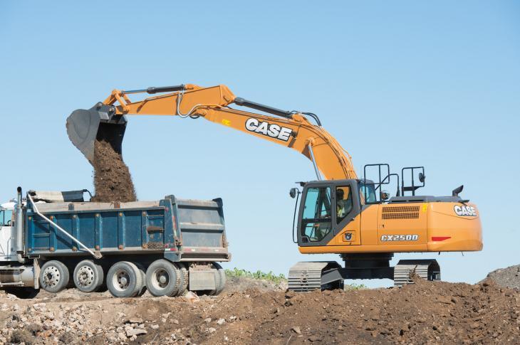 An excavator loads a truck.