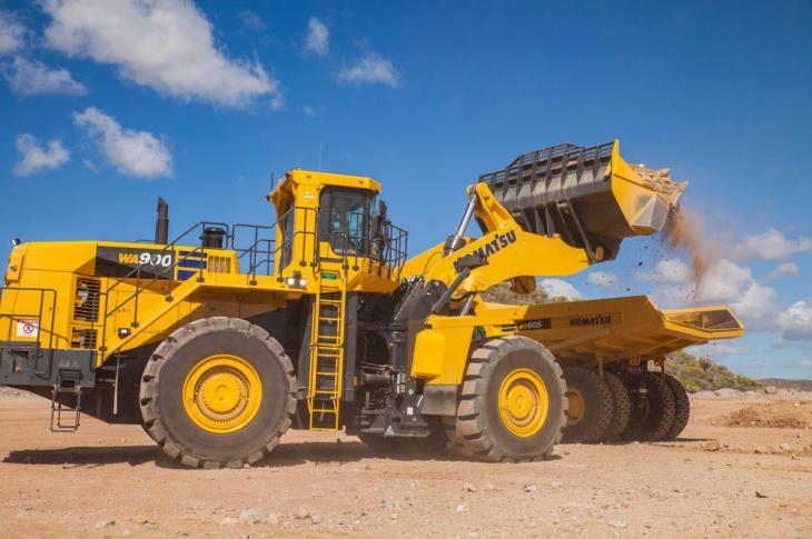 Komatsu WA900-8 wheel loader dumps material into a truck.