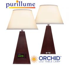 Shown here in a Cherry Wood finish, the Orchid LED table lamp from PURillume shines bright.