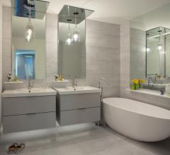 Gray bathroom with two floating vanities and a soaking tub