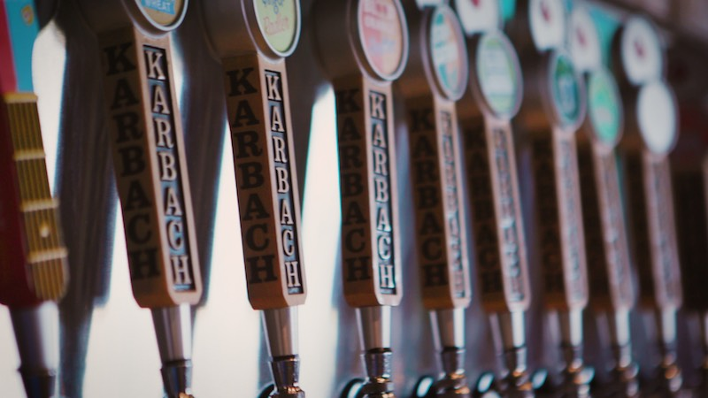 Karbach Brewing Co. beer handles in line along a bar wall