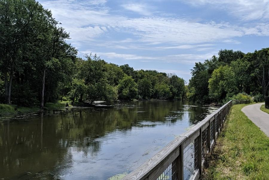 The Des Plaines river flows gently on the left as a bike path curves out of frame to the right.